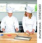 Senior chef teaching newbie female chef, how to roll and knead dough - stock photo