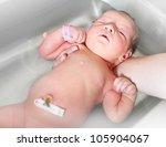 First bathing of a newborn baby girl in a hospital bathtub. - stock photo