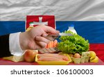 man stretching out credit card to buy food in front of complete wavy national flag of russia - stock photo