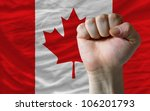 complete national flag of canada covers whole frame, waved, crunched and very natural looking. In front plan is clenched fist symbolizing determination - stock photo