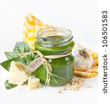 Green pesto sauce on glass jar and ingredients. - stock photo