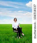 smiley businesswoman sitting in armchair and holding documents - stock photo