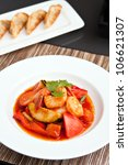 Thai style sweet and sour shrimp dish presented beautifully on a round white plate and pan fried gyoza dumplings. - stock photo