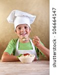 Happy boy with chef hat eating pasta from wooden bowl - traditional food - stock photo