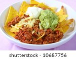 Nachos - corn chips topped with spicy salsa, guacamole, sour cream, and cheese. - stock photo