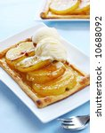 French fruit tart, with nashi asian pears on puff pastry, topped with rich vanilla ice cream.  Focus on the ice cream. - stock photo