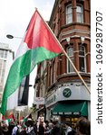 London, United Kingdom, 14th April 2018:- The flag of Palestine at a gathering of protesters along Kensington High Street, near the Israeli Embassy in London to protest the occupation of Palestine. - stock photo