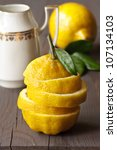 Fresh yellow sliced lemon on a wooden board. - stock photo