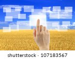 Woman hand pushing virtual icons on interface over wheat field and blue sky landscape - stock photo