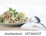 Healthy amaranth grain prepared tabbouleh style with chickpeas, and a lemon wedge - stock photo