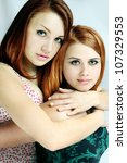 Two red-haired young women hugging each other - stock photo