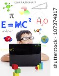 Portrait of smart boy with physics formula and laptop computer - stock photo