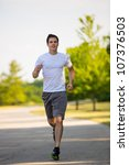Healthy Looking Young Man Jogging in the Woods Under Morning Sunlight - stock photo
