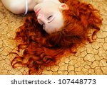 Beautiful young woman with red hair on the dried up ground. - stock photo