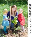 family planting sprouts with  spade outdoor - stock photo
