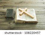 old holy bible and wood cross on rustic wooden table - stock photo