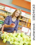 woman choosing apple during shopping at fruit vegetable supermarket - stock photo