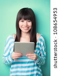 Happy Chinese woman leaning against a wall with a touch screen - stock photo