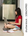 A portrait of a Chinese college student sitting cramming in college coridor. - stock photo