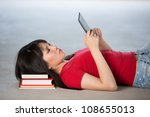 Pretty young Chinese woman lying on the floor with an e-book reader - stock photo