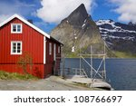 Typical red rorbu fishing hut by the fjord on Lofoten islands in Norway - stock photo