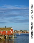 Red fishing rorbu hut by the fjord in town of Reine on Lofoten islands - stock photo