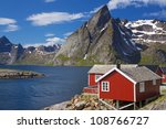 Picturesque red fishing hut on the coast of fjord on Lofoten islands in Norway - stock photo