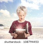 Happy Young Blonde Boy Opening a Gift Box on the Beach - stock photo