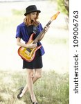 Style redhead girl with guitar at outdoor. - stock photo