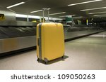 Wheeled suitcase in airport terminal baggage claim area - stock photo