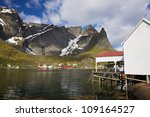 Fishing port in picturesque town of Reine on Lofoten islands, Norway, surrounded by rocky cliffs - stock photo