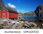 Typical red shed on the coast of fjord on Lofoten islands in Norway - stock photo