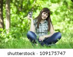 Teen girl with camera at the green park. - stock photo