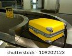 Wheeled luggage on airport conveyor belt - stock photo