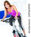 Beautiful woman at the gym on bike - stock photo