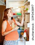 pregnant woman putting cheese into refrigerator  at home - stock photo