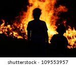 Two children looking at big fire - stock photo