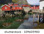 Typical red rorbu fishing huts on Lofoten islands in Norway reflecting in fjord - stock photo