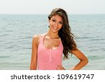 Portrait of a beautiful woman with long pink dress on a tropical beach - stock photo
