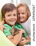 Happy kids holding their new pet - a little kitten asleep in their arms - stock photo