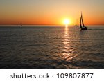 The gold silhouettes of boats at sea with sunset - stock photo