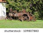 Old rusty farming tractor near barn - stock photo