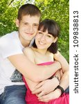 Beautiful young couple sitting arm in arm - stock photo