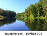 Tranquil landscape with a lake and pine forest - stock photo