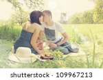 Young couple on a picnic with wine - stock photo