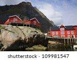 Traditional red fishing rorbu huts built on rocks on Lofoten Islands, Norway - stock photo