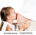 beautiful little girl kisses a stomach of pregnant mother - stock photo