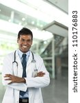 Male Indian doctor wearing a white coat and stethoscope. - stock photo