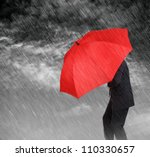 Businessman with red umbrella protecting himself from the storm concept for protection from recession or economic depression etc - stock photo