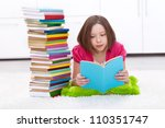 Young girl with lots of books reading on the floor - stock photo